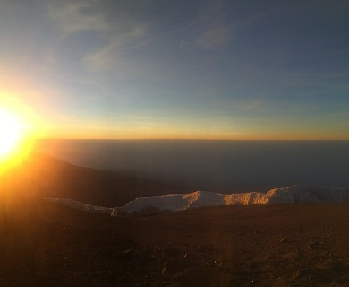 In this Kilimanjaro summit sunrise image, the sun is just over the horizon as the team sat just past Stella Point.  The sun is a brilliant orange and yellow on the left hand side of the photo, largely obscuring a smaller peak that was behind them as they climbed. Above the horizon is a thin orange line, then shades of blue from light to dark.  Below is some deep lavender, down to glacier, then martian red soil.