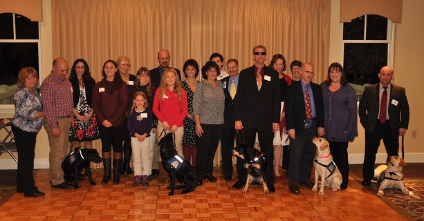Scene near the podium from the 2014 Peak Potential dinner: Some 15 to 20 volunteer puppy raisers for Guiding Eyes for the Blind, and five of their potential future Dog Guides, line up across the front of the room for a fun group photograph.