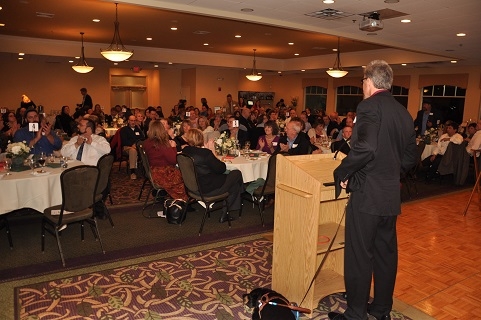 Photo is of Randy at podium, addressing attendees after dinner at the 2014 event, with dog guide Autumn at his feet to his left.
