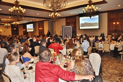 photo shows Randy at the podium addressing a very large crowd at the 11/14 Sixth Annual Peak Potential Dinner and Charity Auction. Video screens with a Kilimanjaro image are to either side of Randy.