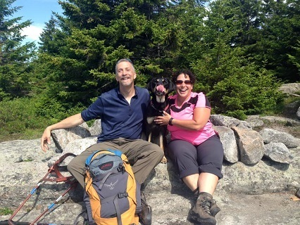 Randy, Autumn (with tongue out) and Tracy sit near the summit of Mt. Piper on what appears almost to be a couch made of stone on a sunny summer day.